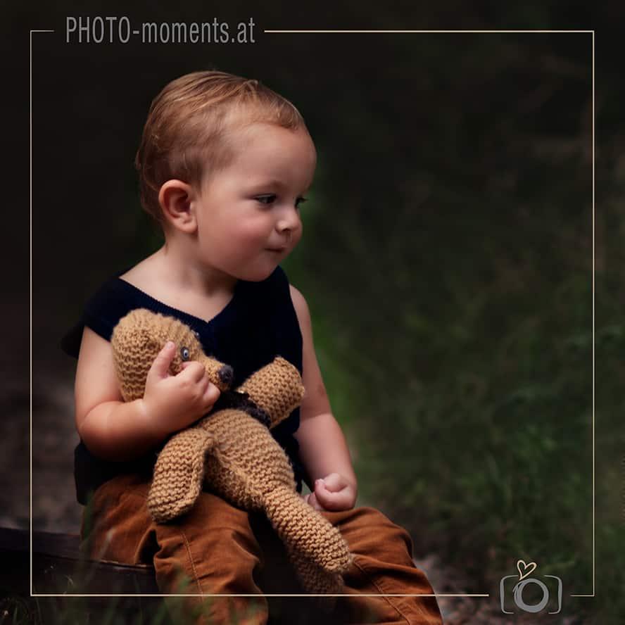 Baby sitzt am Boden mit einem Teddybär